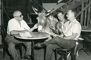 Men sitting around a card table with a donkey