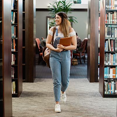image of student walking through library stacks