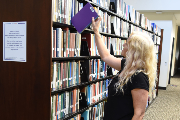 Image of a librarian removing book from shelf