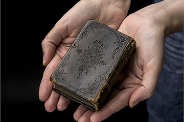 Small book held with two hands.